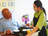 caregiver giving meals to patient