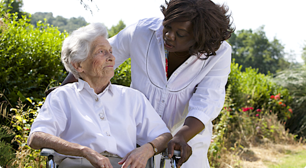afro-american caregiver talking to a disabled senior womang